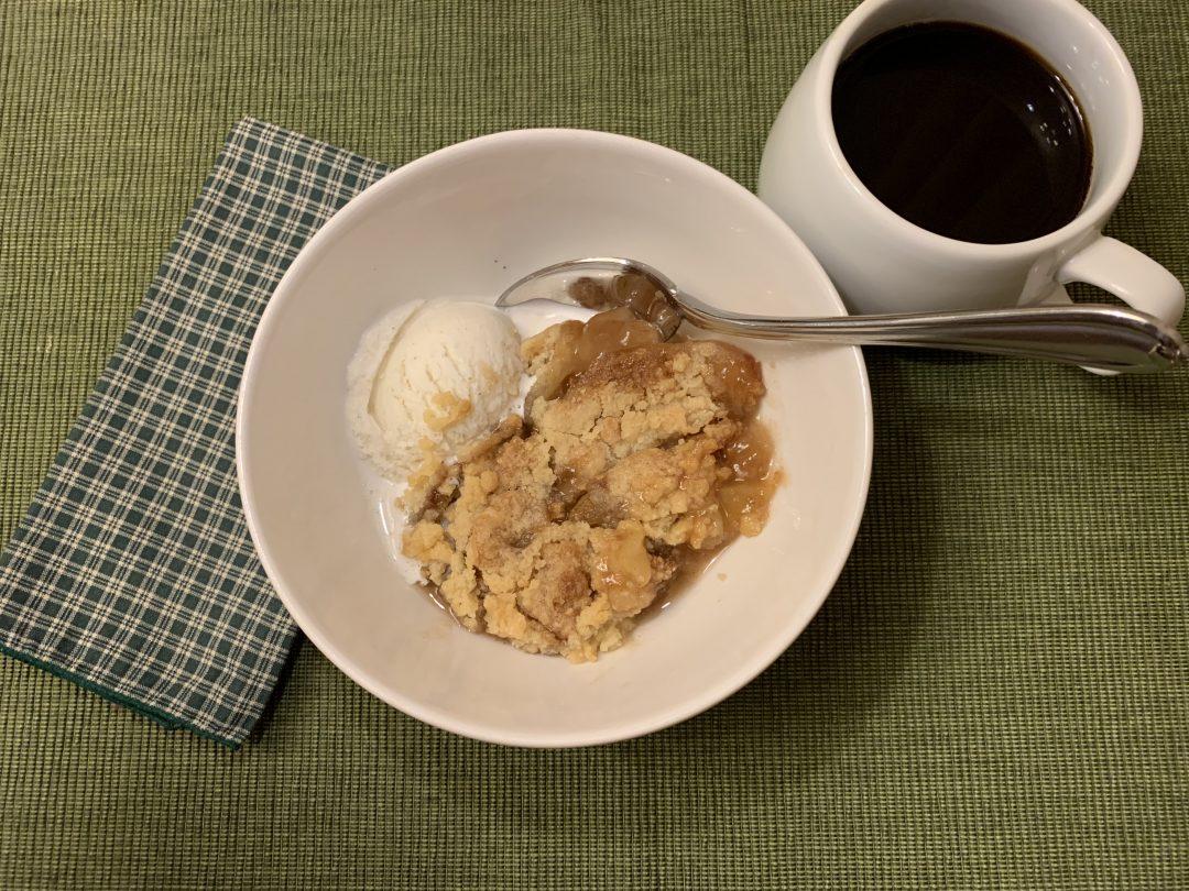 apple crisp plated with vanilla ice cream and coffee