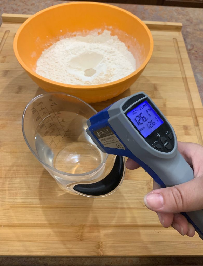 checking the temperature of the water with a digital temperature gun