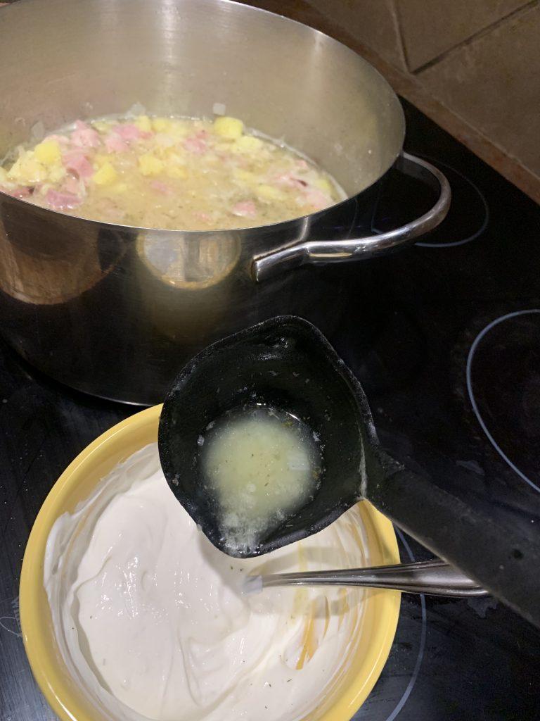 pouring hot soup mixture into sour cream mixture