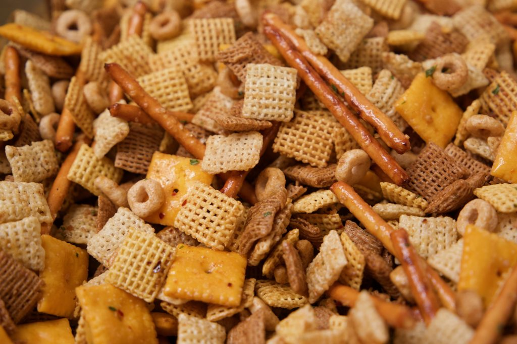 mixing the sauce onto the spicy Chex mix