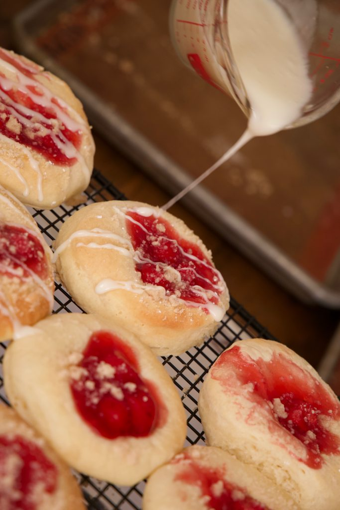 drizzling the icing over the kolaches